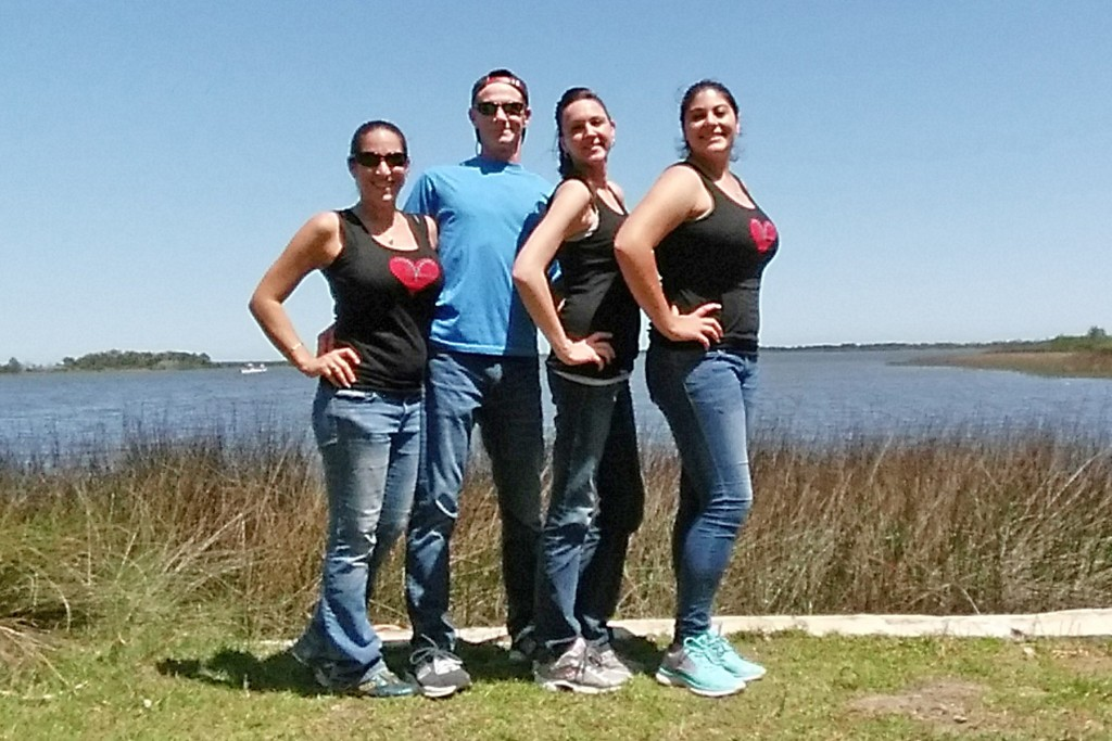 Rusty hiking with his three friend girls who are wearing their Vicki's Vheart tank top, have stopped by the river for a photo