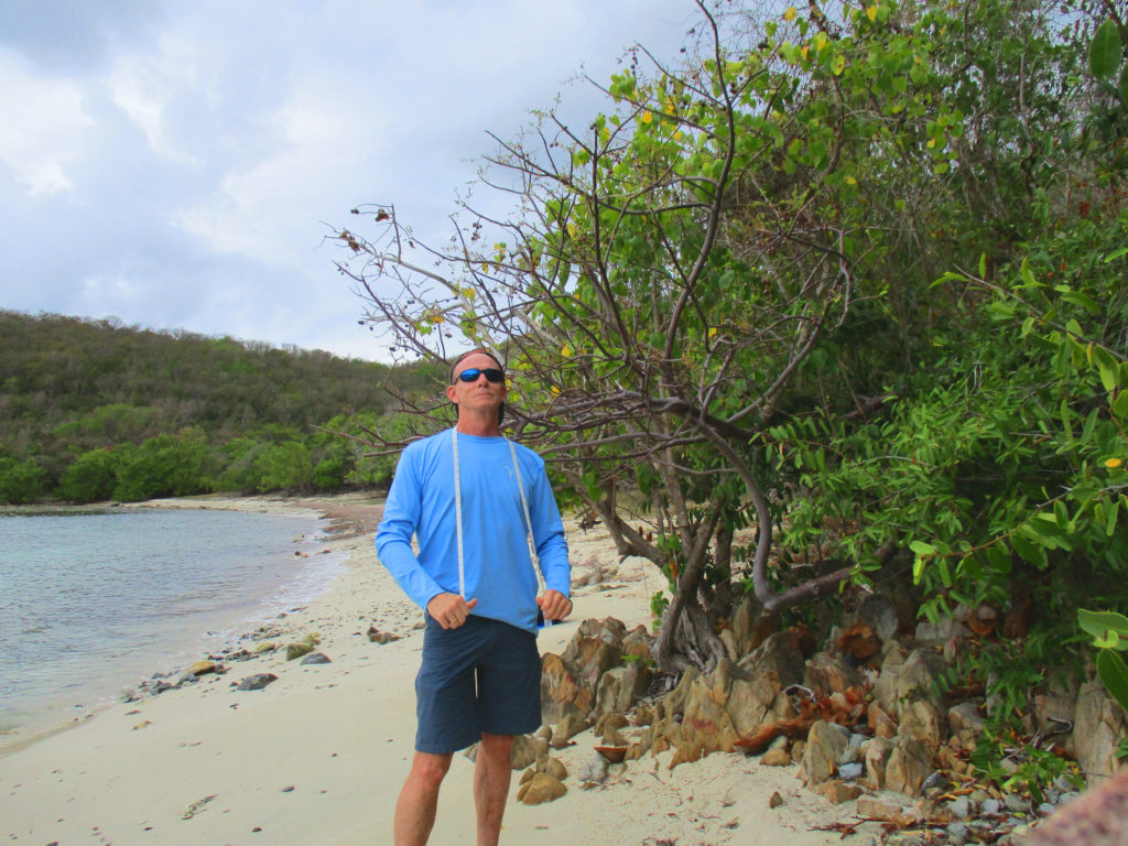 Rusty in Vicki's fishing shirt with tape measure around neck on beach in St. John