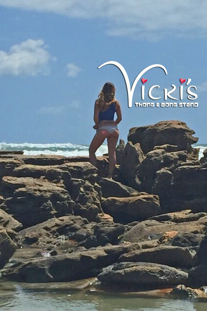 Back view of Jen as she stands on the rocks gazing out over the ocean with her V-Heart Tattoo on her left bun cheek