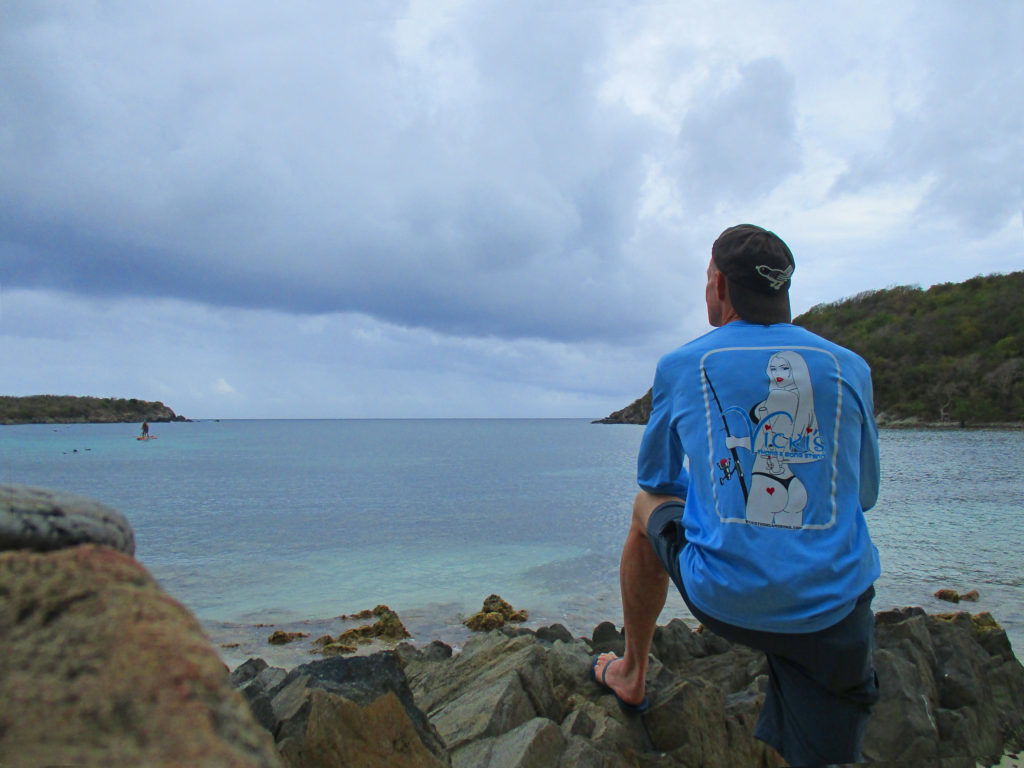 Rusty on beach rocks looking out over St John and the Caribbean in his long sleeve Vicki's fishing shirt