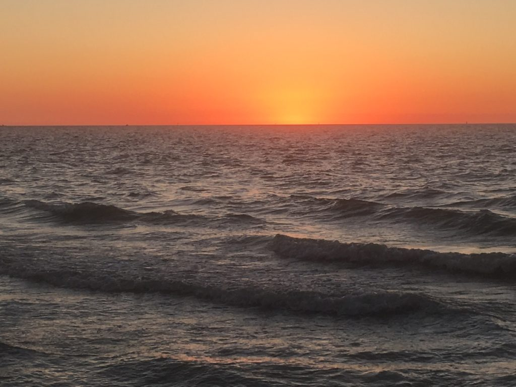 The afterglow of a perfect sunset off of pass-a-grille beach warms the waves in the gulf after a great photoshoot