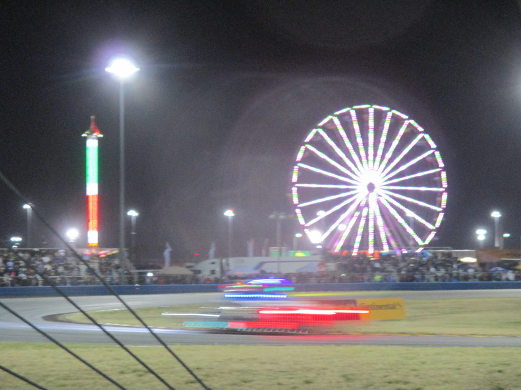 Night racing at the Daytona 24 hour showing blurred car approacing turn with lit up ferris wheel in background