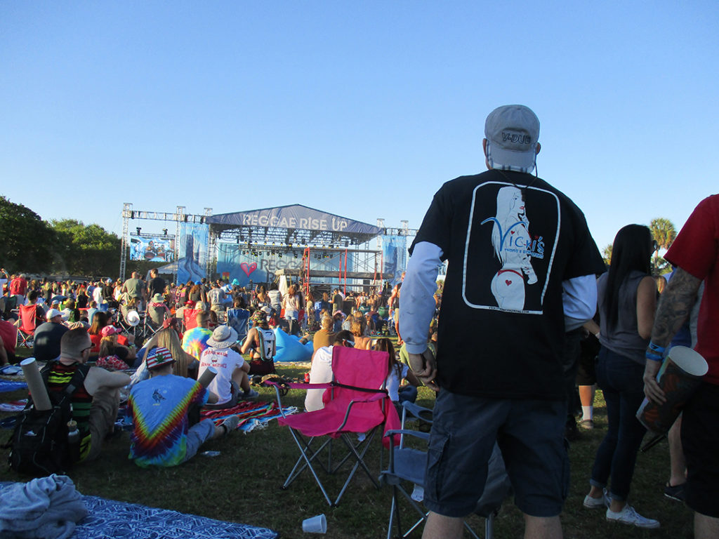 Looking at the outdoor Reggae Rise Up stage with a fan wering an original Vicki's girl shirt ready for some music