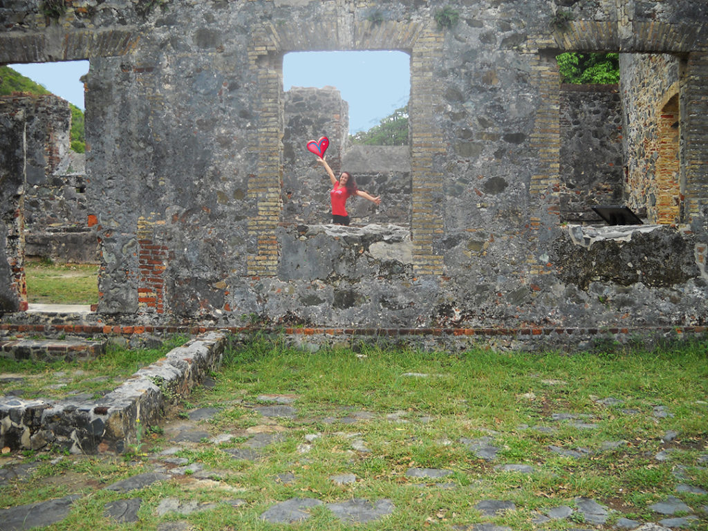 Beautiful girl posing in sugar ruins in the USVI with arm up holding a big heart