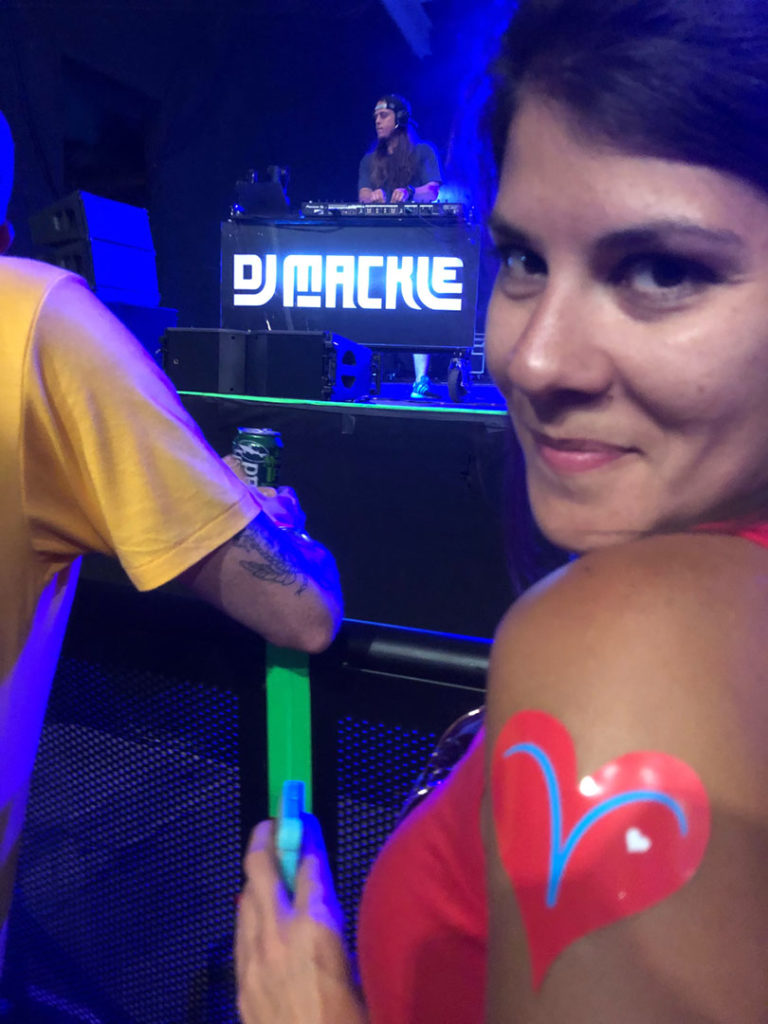close up of pretty girl with the Vicki's Vheart sticker on her upper shoulder, the stage with dj mackle in the background, and a playful look in her eyes