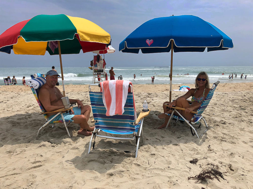 on the beach at Ocean City with umbrellas up, chairs out, and calm ocean