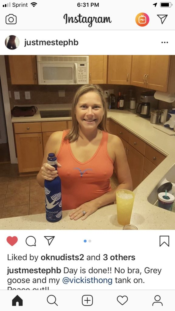 Steph in kitchen wearing her Vickis coral tank top, no bra, and a bottle of grey goose ! Wow !